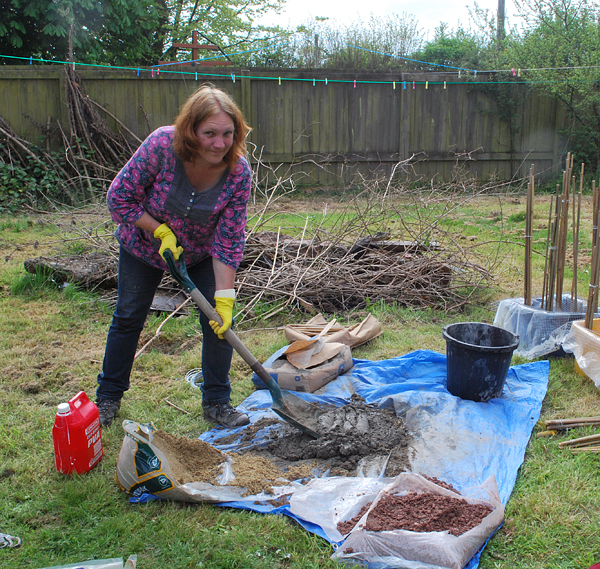 Here I am mixing concrete to set the bamboos into.